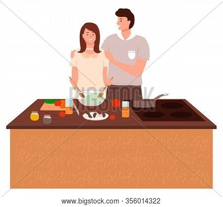 Couple Stand Together By Table On Kitchen. Man Hugging And Helping Woman. Housewife Preparing Vegeta