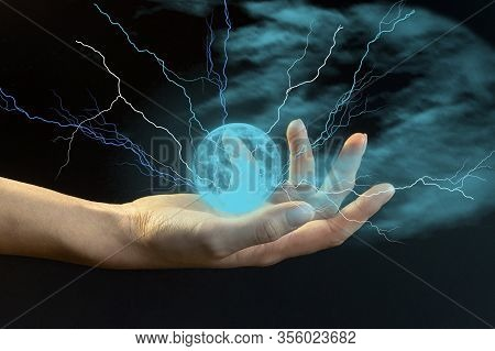 A Young Girl Holds A Ball Of Lightning In Her Hand Against A Dark Background Of Blue Misty Clouds. T
