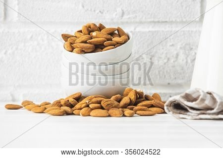 Dried almonds nuts in bowl on white table before white brick wall.