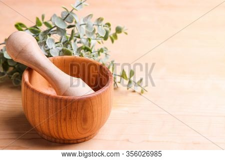 Wooden Mortar With A Pusher And A Branch Of Eucalyptus On A Wooden Background.