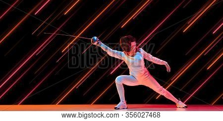 Creative Sport And Neon Lines On Dark Background, Flyer, Proposal. Female Fencing Player Training In