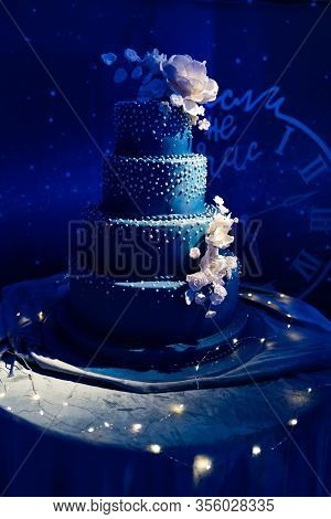 Dark Blue Multi-tiered Wedding Cake Decorated With Sugar Beads And Flowers In The Dark