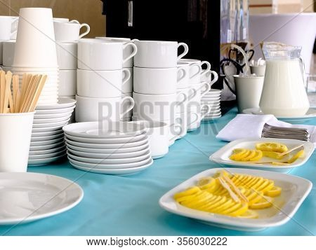 Piles Of White Ceramic Cups And Saucers On Display. On Plates Are Thinly Sliced Lemons. In A Glass J