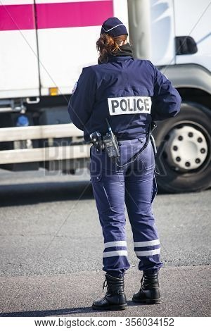 Policeman On A Street In Paris Controls Public Order. A Fully Equipped Woman Policeman Monitors Traf