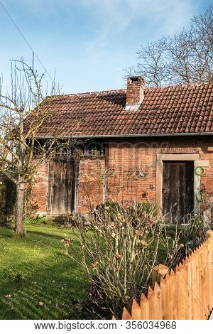 Little Brick House With A Small Garden, Tree And Fence