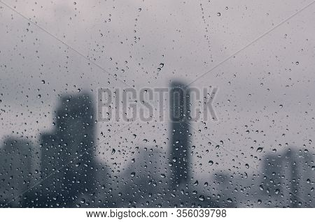 Rain Drop On Glass Window In Monsoon Season With Blurred City Buildings Background.