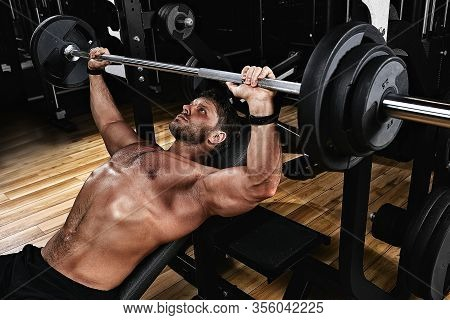 Young Muscular Man Lifting A Barbell Bench Press In The Gym. Sport, Movement, Life. The Concept Of A