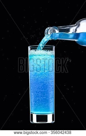 Alcoholic Carbonated Drink Of Blue Color Flows From A Bottle Into A Glass.