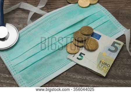 Medical Face Mask On A Wooden Table With Euro Coins And A Five Euro Banknote On Top Of It. Concept I
