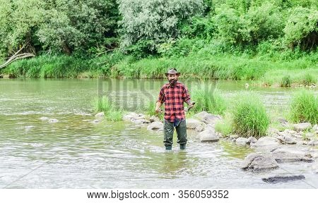 Fisher Masculine Hobby. Fish On Hook. Brutal Man Wear Rubber Boots Stand In River Water. Satisfied F