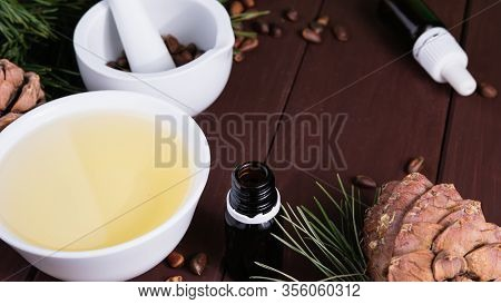 Cedar Oil In A Glass Bottle And Cedar Cones With Nuts On A Old Wooden Table. Top View