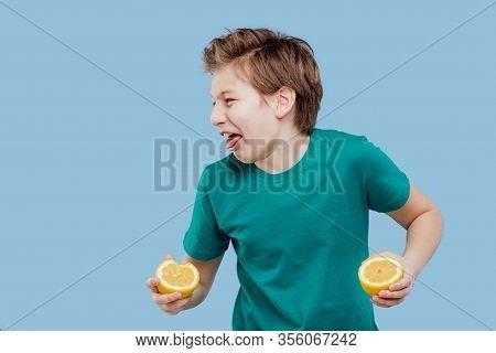 Boy Taste A Fresh Lemon, Sour Taste, Make Grimace, Facial Emotions Negative, In Green T-shirt Isolat
