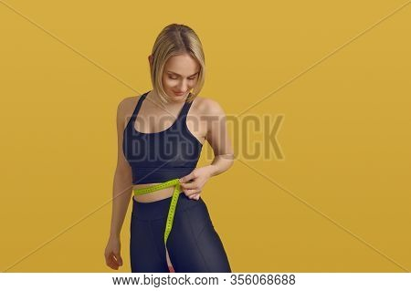 Slim Sporty Young Woman Measuring Her Waist With A Tape Measure As She Looks Down With A Satisfied S
