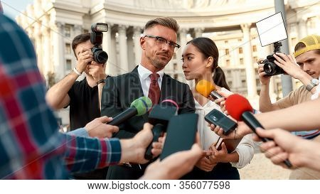 Horizontal Shot Of Politician Consulting With His Assistant While Giving Interview To Reporters. Peo