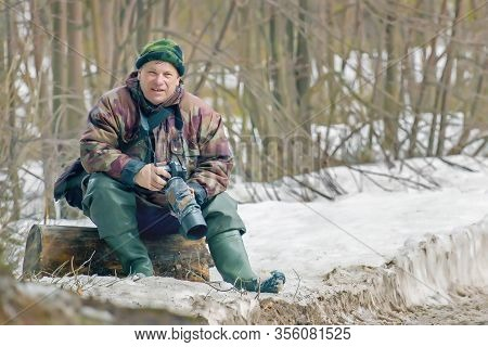 Adult Male Professional Nature Photographer At A Halt In The Outdoor In The Winter Forest