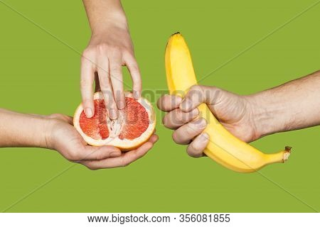 Banana And Grapefruit In Hands Isolated On A Green Background As A Symbol Of Male And Female Masturb