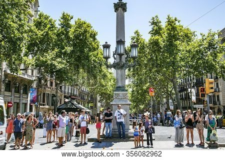 Spain, Barcelona, July, 15, 2017 - View Of The La Rambla Street With Walking Pedestrians And City Gu