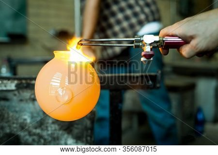 A Close Up Selective Focus View On The Hands Of A Glassblower At Work With A Molten Glob Of Glass On