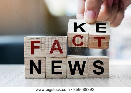 Businessman Hand Holding Wooden Cube With Flip Block Fake To Fact News Word On Table Background. New