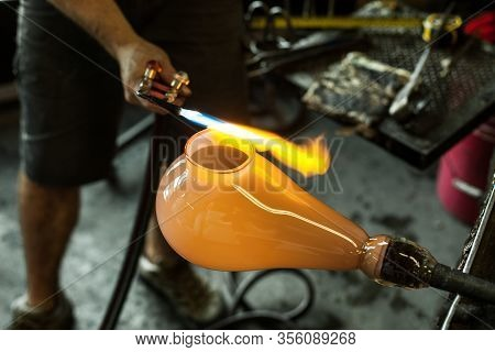 A Close Up High Angle Shot Of A Traditional Glassblower At Work Crafting A Blown Glass Lantern, Heat