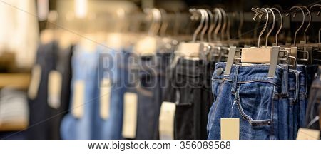 Jeans Or Denim Pants (trousers) Hanging On Rack In Clothes Shop. Fashion Product Collection In Cloth