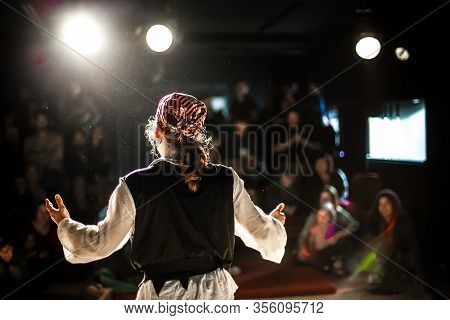 A Selective Focus View From Behind An Actor Dressed In Pirate Costume, Performing On Stage To A Crow