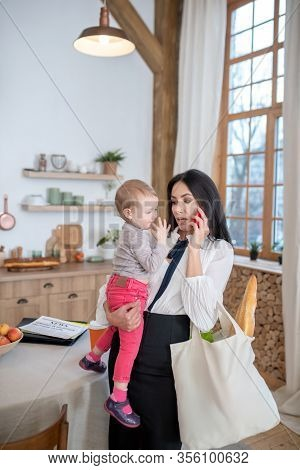 Mom Holding Daughter And Shopping Bag, Talking On The Phone