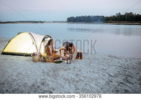 Young Couple Sitting At The Campsite On The Beach, Man Kindling Fire