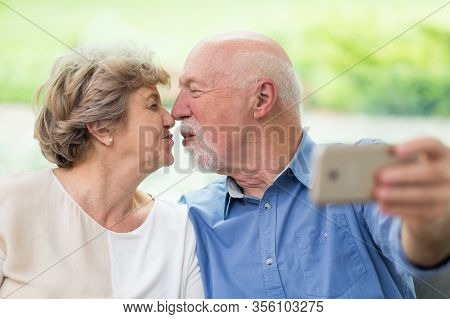 Cute Elderly Couple Kissing In Front Of A Mobile Phone While Taking Selfie