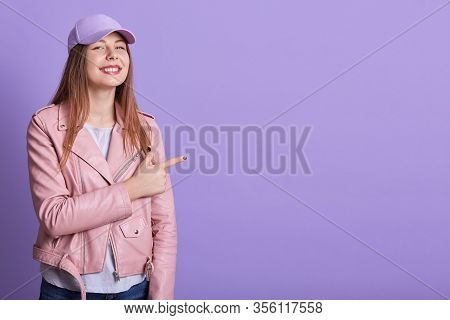 Photo Of Nice Woman Wearing Cap And Leather Jacket Pointing Fingers And Looking Aside, Satisfied Fem