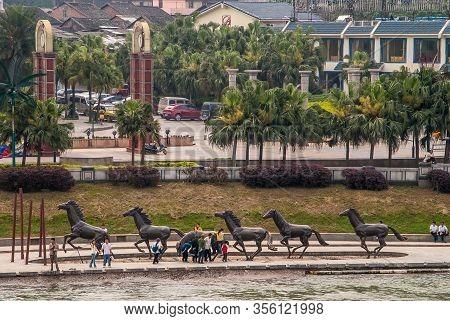 Guilin, China - May 11, 2010: Li River Downtown. Long Group Bronze Statues Of Running Horses Along S