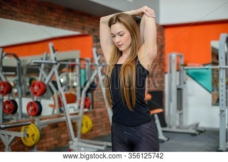 Portrait Of Fitness Woman Stretching At Gym Before Workout. Female Stretch Back Of Upper Arm, Tricep