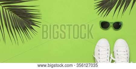 White Female Fashion Sneakers, Trendy Sunglasses, Tropical Leaves On Green Background. Flat Lay Top
