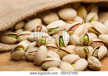 Unpeeled Green Pistachios In A Burlap Sack And On A Wooden Table