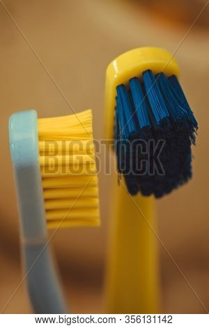 A Blue Toothbrush With Yellow Bristles And A Yellow Toothbrush With Blue Bristles. Closeup Of Toothb