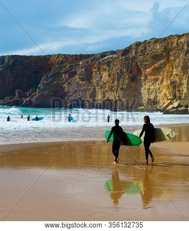 Surfers With Surfboards On The Beach. Algarve, Portugal