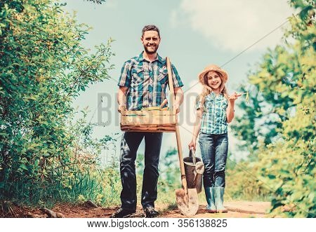 Father And Daughter With Shovel And Watering Can In Garden. It Is Time To Plant Prepare Beds And Car