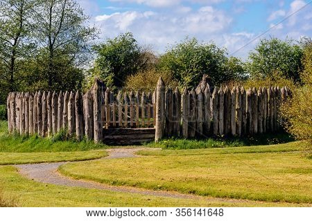 Old Wooden Palisade Of The Fort Or Camp Surrounded By Green Fields And Trees. Depicting Early Age Of
