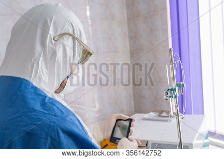 Doctor In Protective Suit With Pda In The Hands Works At Pandemic Period. Epidemic Disease Concept.