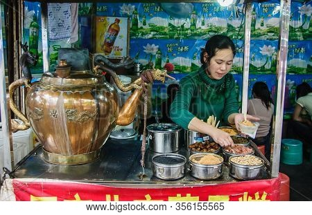 Guilin, China - May 10, 2010: Downtown. Woman Scoops Fast Food In Cup At Her Booth With Giant Dragon
