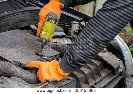 Male Auto Mechanic Unscrews A Nut On A Car Engine With A Screwdriver