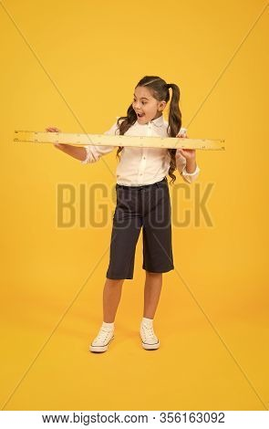 What A Reason For Sirprise. Surprised Pupil Or Young Learner. Cute Pupil Holding Long Ruler On Yello
