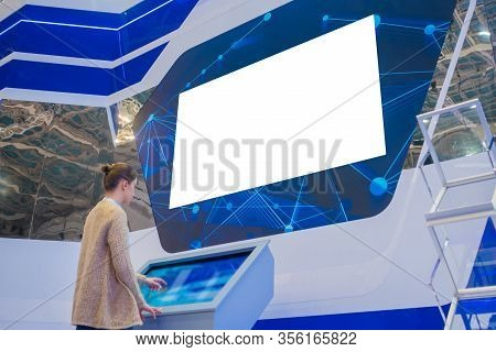 Woman Looking At Blank Large Wide Interactive Wall White Display At Modern Technology Exhibition Or
