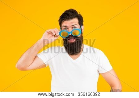 Accessorize Your Eyesight. Cool Guy Wear Eyeglasses Yellow Background. Hipster Look Through Fancy Ey