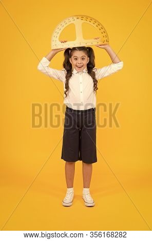Measuring And Calculating. Small Schoolchild Holding Protractor For Measuring Angles On Yellow Backg