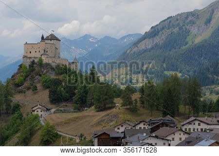 Small Mountain Village And A Castle On The Top Of A Natural Hill At Cloudy Day With Swiss Mountain P