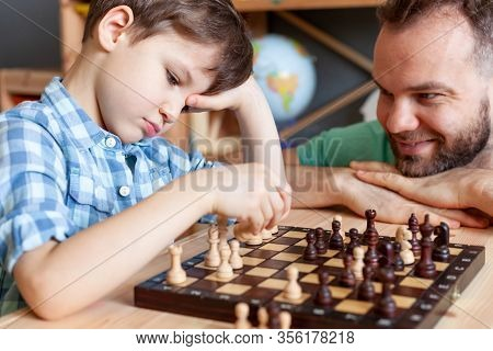 Son Is Engaged In Chess With His Father