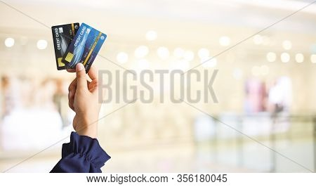Close Up Of Hand Woman Holding Credit Card For Shopping With Abstract Blur Mall Background. Business