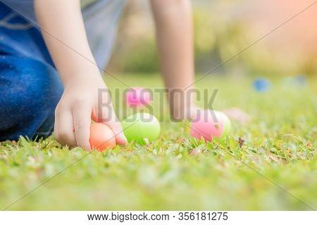 Little Boy Hunting For Egg In Spring Garden On Easter Day.