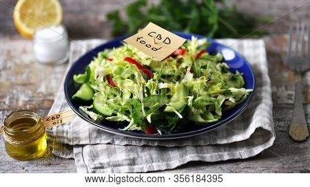 Selective Focus. A Note With The Words Cbd Food In A Plate With Vegetable Salad. Salad With The Addi